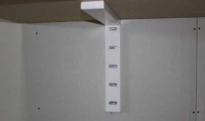 A white heavy–duty hybrid bracket underneath a wall mounted tabletop closeup shot